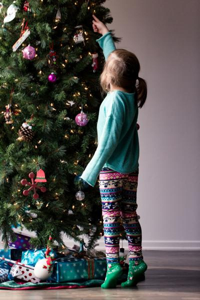 Young girl decorating a Christmas tree