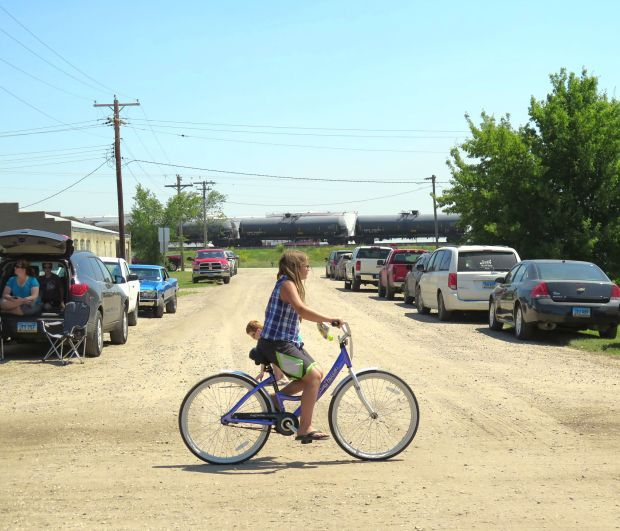A girl rides a bike past an oil train