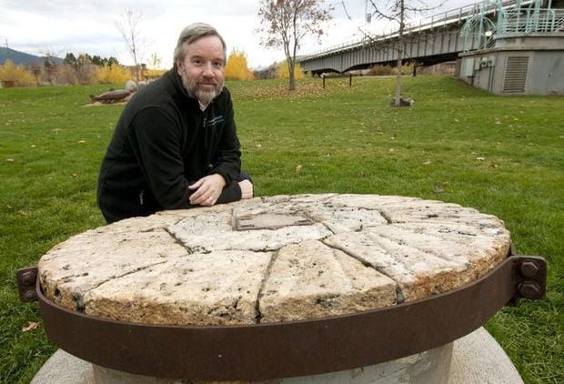 Ken Egan Jr. kneels by the millstone in Caras Park