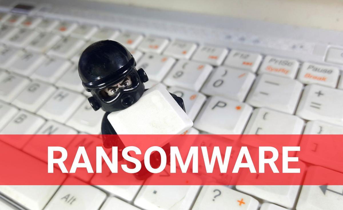 Cyber security concept. Figurine holding keyboard button with word ransomware