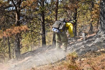 A wildland firefighter works the North Hills Fire