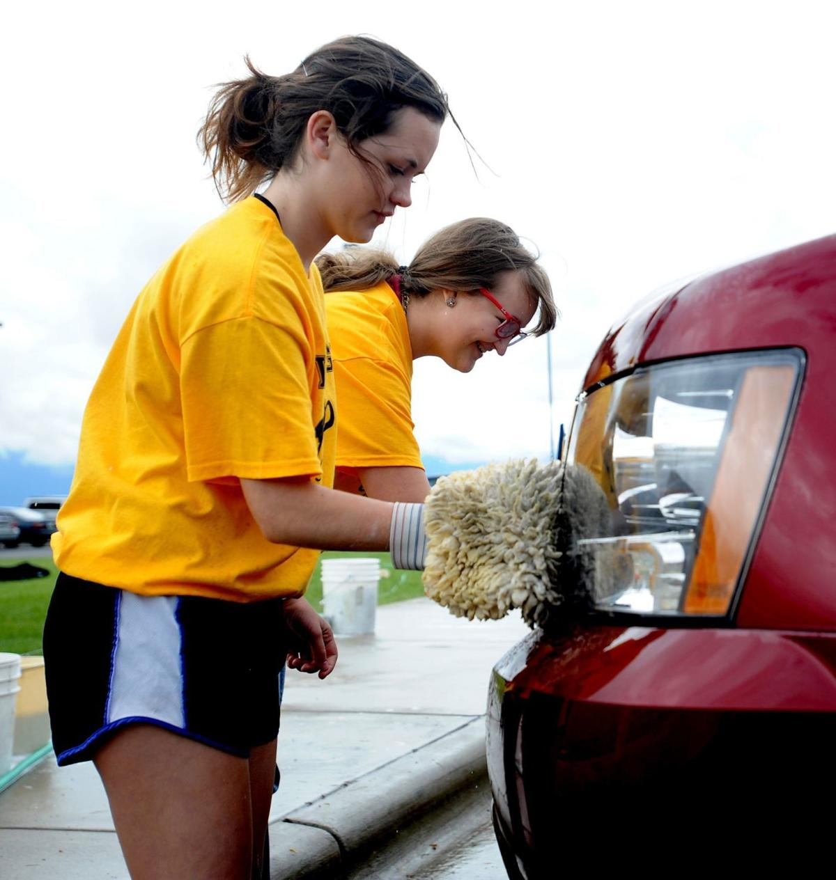 Casey Nelson and Madison Nelson wash a car