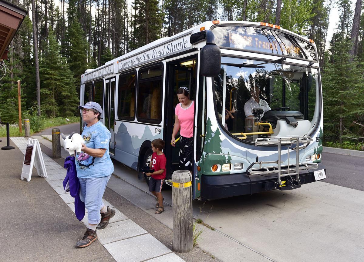 Glacier National Park visitors get off one of the park's free shuttles
