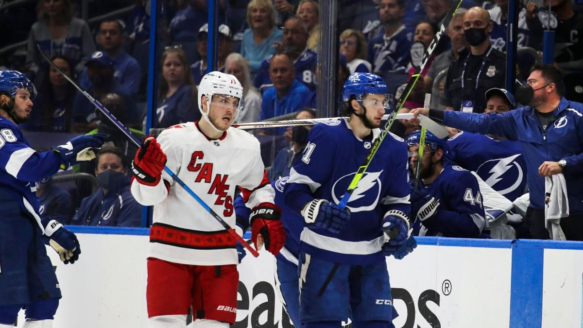 Lightning defenseman Mikhail Sergachev, in background on left, gets handed a stick after his broke while on the ice against the Hurricanes in the first period of Game 3 in Tampa.