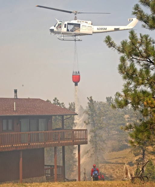 A helicopter makes a water drop at a home