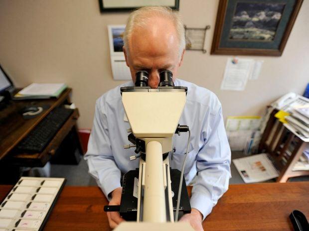 Dr. Duane Schultz examines cancerous skin cells