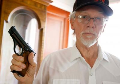 Dick Gessell poses with a 9mm pistol