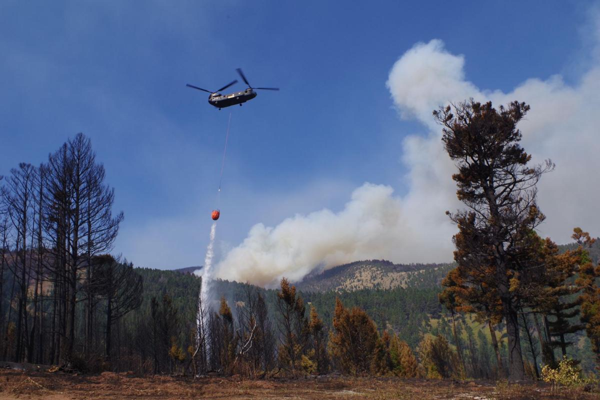 A Chinook helicopter dumps 2,000 gallons of water on the Alice Creek Fire.