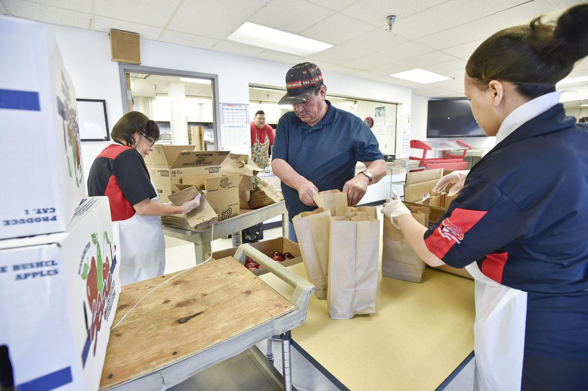 School cooks and volunteers bag five hundred breakfasts and lunches