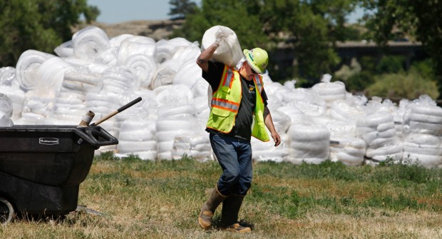 A worker from Enviro Care carries a roll of absorbant pads