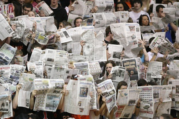 Billings Senior students hold up newspapers