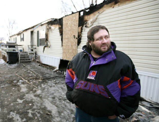Victor Bachmeier stands in front of his home