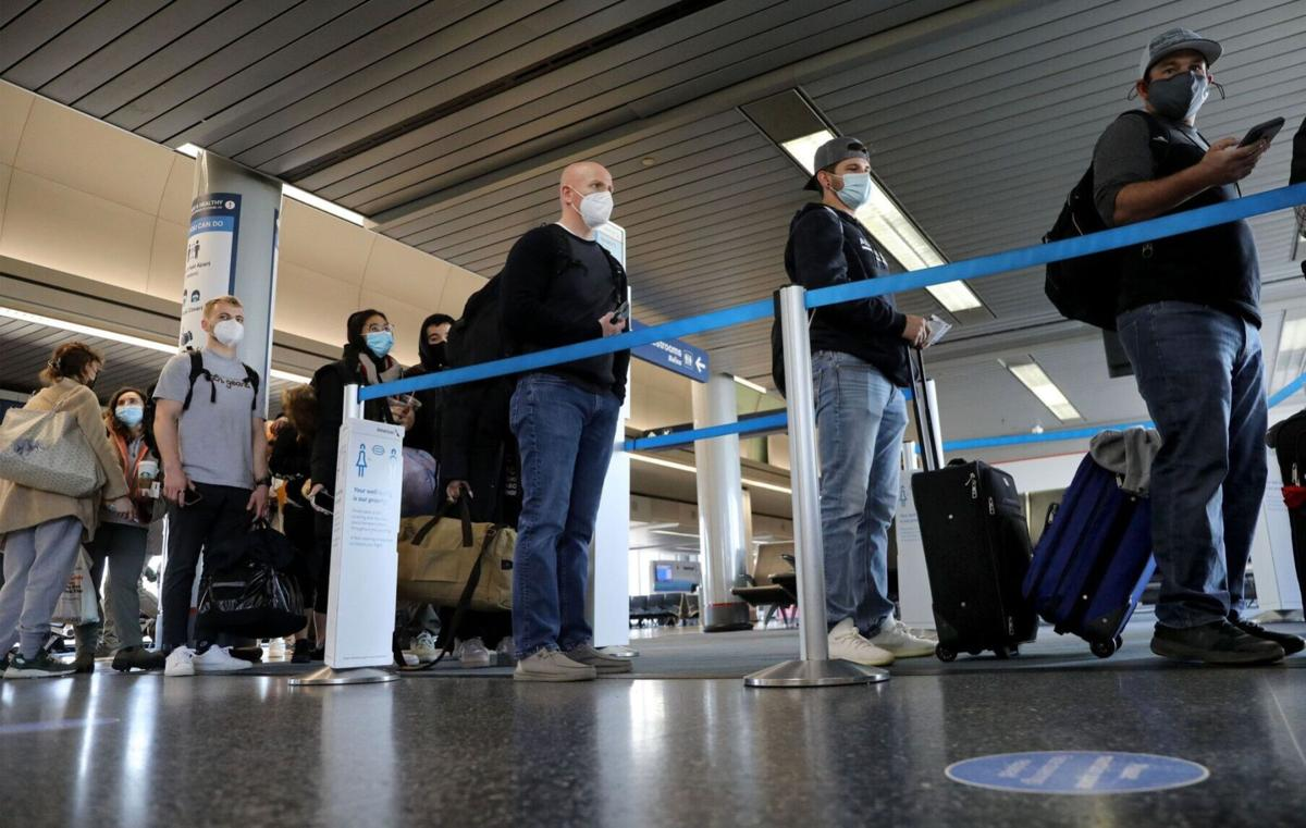 Air travelers line up to board an American Airlines flight to Jackson Hole, Wyoming, at O'Hare International Airport on March 11, 2021.