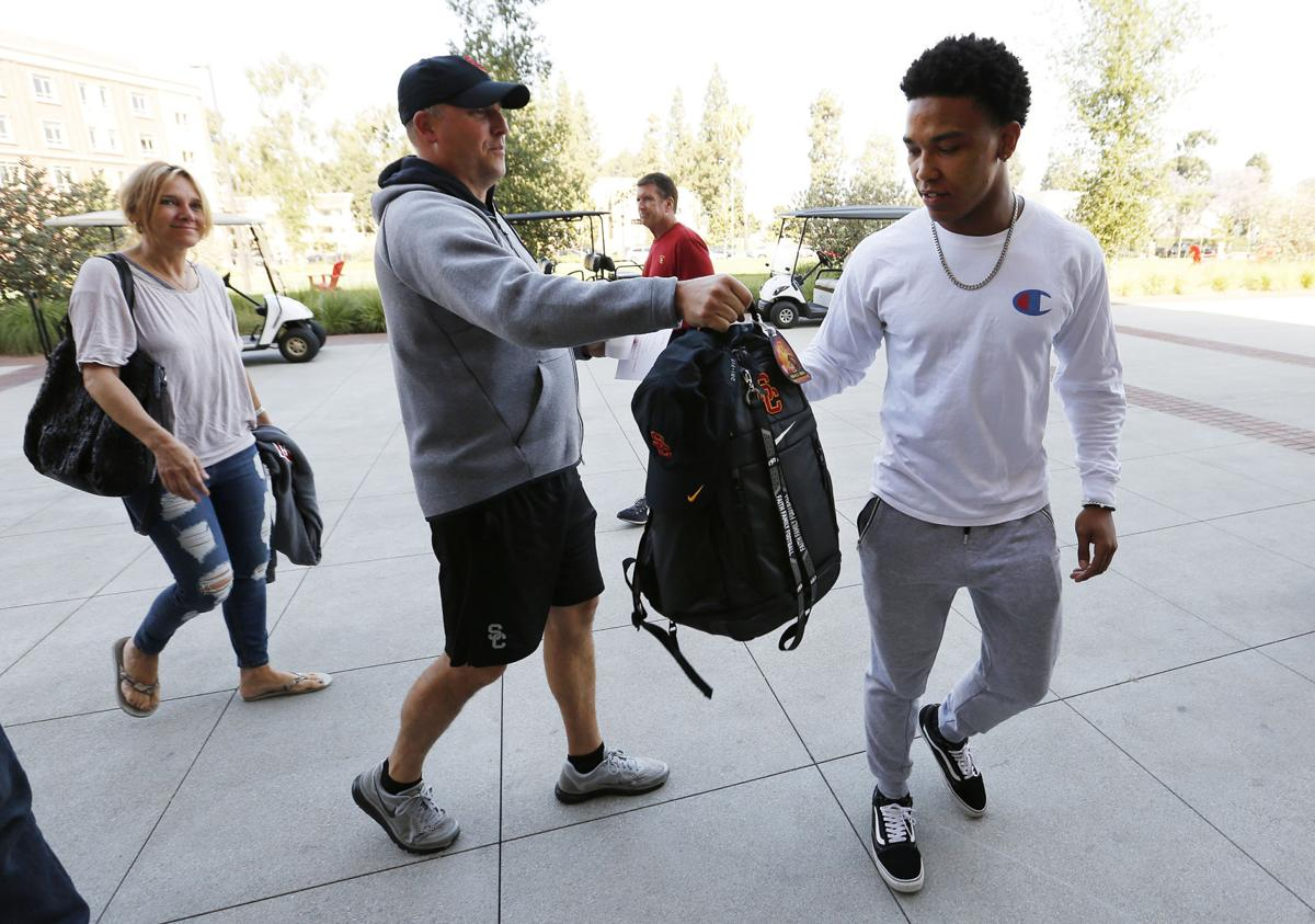 Incoming USC freshman football player Amon-Ra St. Brown, left, is greeted by Clay Helton, Head Coach for the USC Trojans who heads him a backpack as he is helped by his father John Brown and mother Miriam Brown as he moves into his dorm for summer session on June 8, 2018.