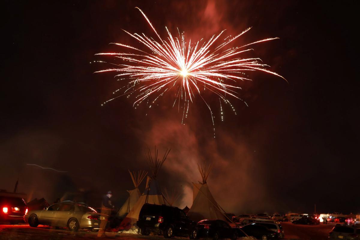 Fireworks explode above tipis inside of the Oceti Sakowin camp