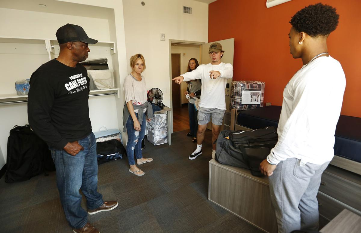 Incoming USC freshman quarterback J.T. Daniels, center, talks about moving furniture as he and roommate wide receiver Amon-Ra St. Brown, right, check out their new dorm room as their family moves them in on June 8, 2018.
