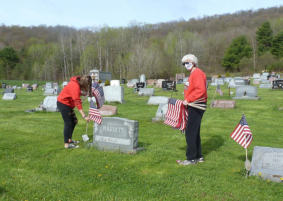 Volunteers honor veterans with American flags before Memorial Day