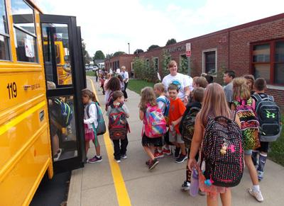 6753e925baa5b Allegany-Limestone Elementary School students are helped by teachers with  boarding buses after the first day of classes on Tuesday.