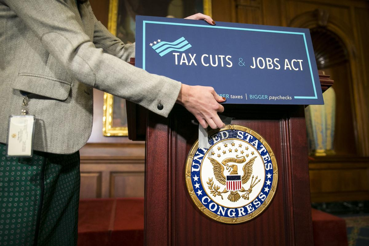 A sign is applied onto a lectern before a news conference following the House passing the Republican-led tax reform bill, on Capitol Hill in Washington.