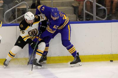 Sabres prospect left wing Brett Murray (57) gets tied up with Bruins prospect defenseman Andrew Peski (78)