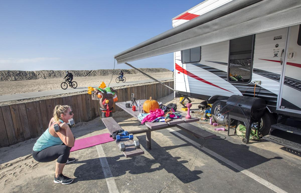 Leah Llere does a high intensity interval training workout outside her RV camper at Dockweiler Rv Park in Playa del Rey, California on Nov. 25, 2020.