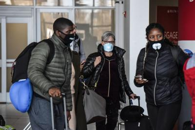 People wear masks at JFK Airport in New York, Feb. 27, 2020. (Stephanie Keith/The New York Times)