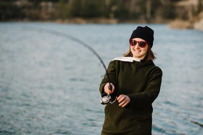 Fisherman with rod, spinning reel on the river bank. Fishing for pike, perch, carp. Woman catching a fish, pulling rod while fishing at the weekend. Girl fishing on lake, pond with text space.