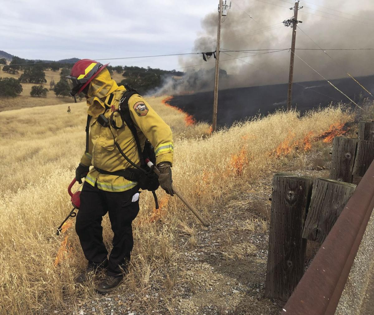 A Cal Fire firefighter torches dry grass near Glory Hole Recreation Area at New Melones in a prescribed burn to protect the community of Angels Camp from a potential wildfire.