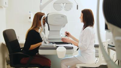 Ophthalmologist,Examining,Young,Woman's,Eyes,In,Medical,Center