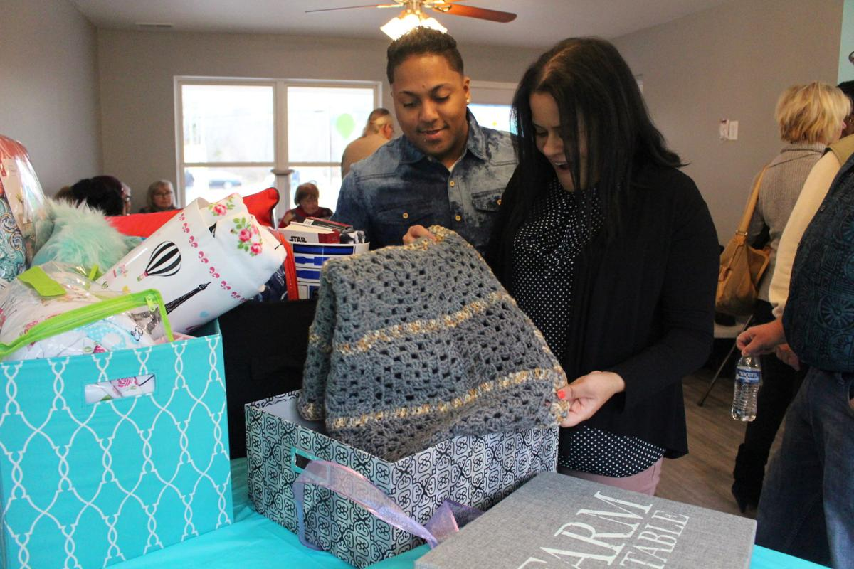 USE2.OPENING.Abigail Garcia and Angel Santiago open housewarming gifts in their new Habitat for Humanity house in Whitesboro Feb. 10.JPG