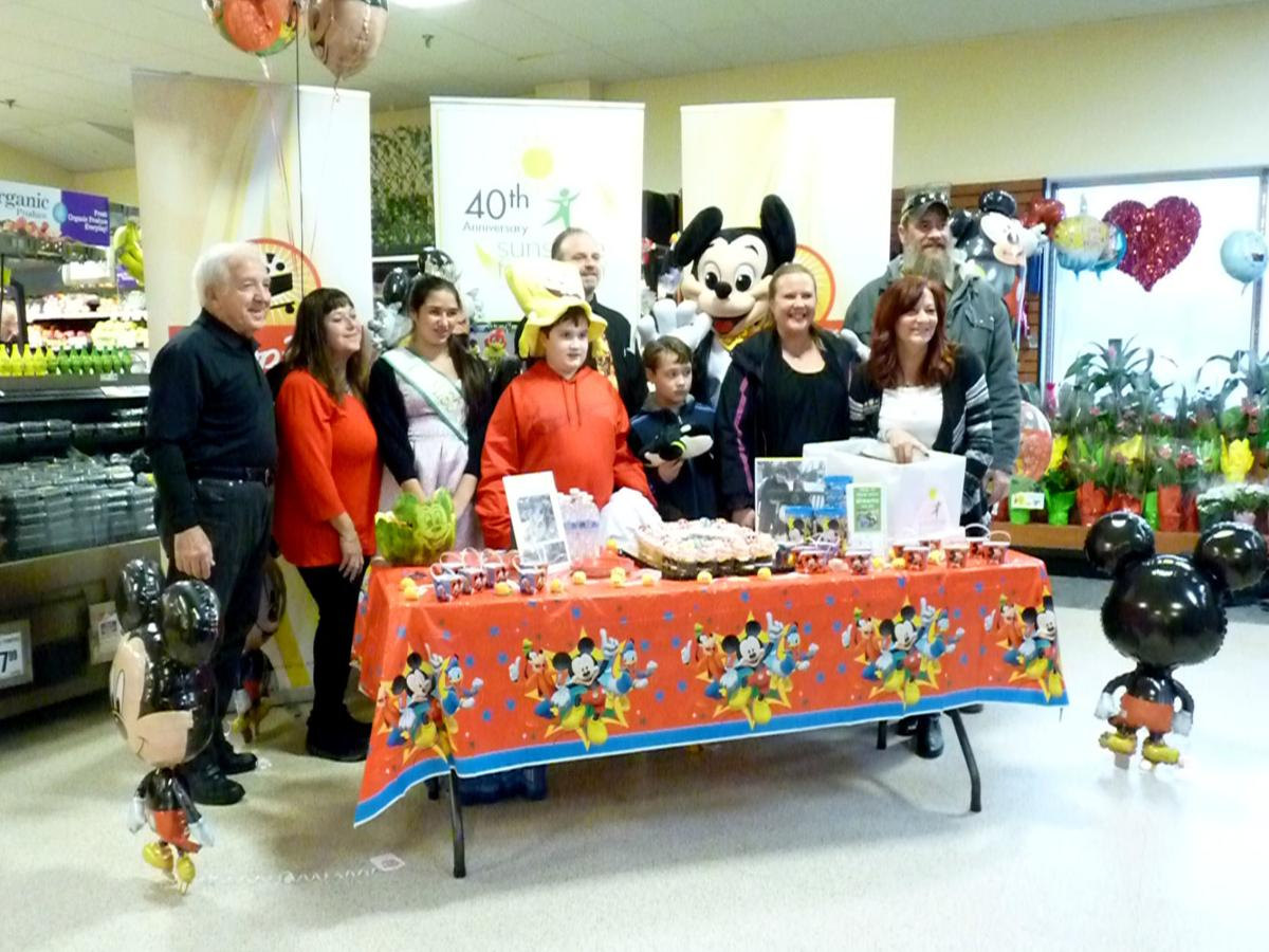 Mark, center (wearing red), stands with his family, members of ShopRite of Rio Grande and members of Sunshine Foundation just moments after finding out his wish has been granted and he is going to Walt Disney World.