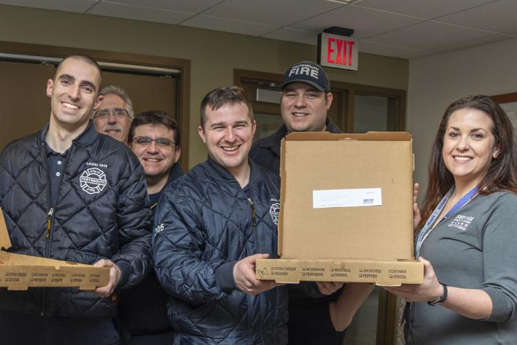 Service Credit Union's Jaime Yates (r.) presents a surprise pizza delivery to Portsmouth firefighters.