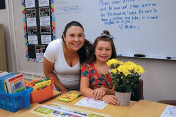 ourth-grade student Ella Galindo gives flowers to her teacher Amanda Avila
