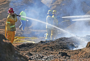 Three firefighters continue to pour water on dozens of mulch piles