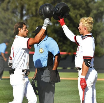 Ayala High's Luke Solis, left, is greeted by teammate Troy McCain