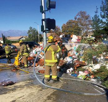 A Chino Valley Fire District firefighter sprays water on trash