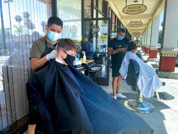 Barbers Rafael Ponce (left) and Omar Gutierrez