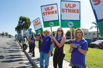 Nurses hold union signs on the sidewalk
