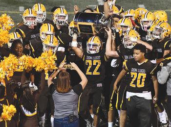 Don Lugo High football players hoist the Milk Can Trophy