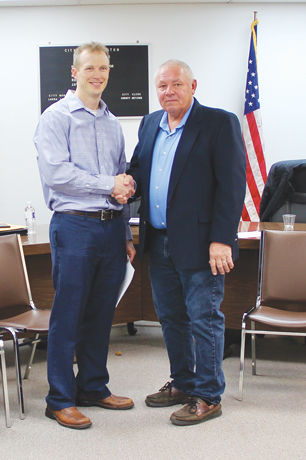 New member Michael Loew shakes hands with Mayor Manser