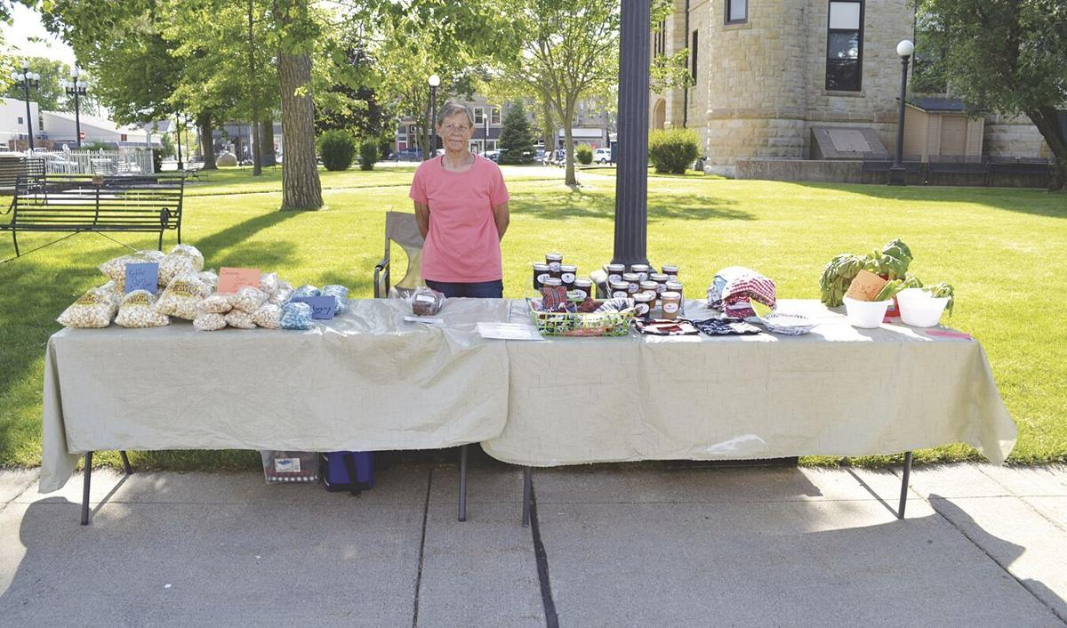 Kathy Dolan standing by tables of items.tif