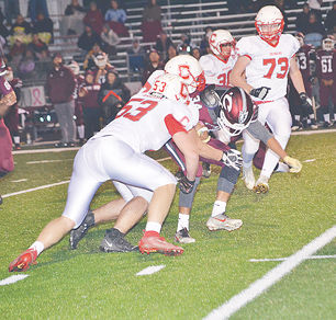 Hunter Koehn and Jordan Mundy tackle a Clarke ball carrier
