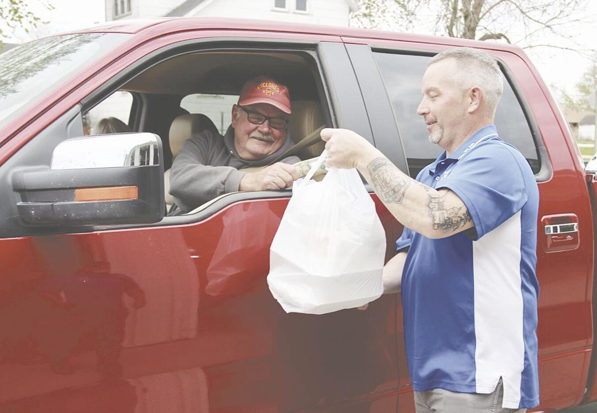 Russell Fire Chief Jeff Neer handing meal to Terry Faulkner.tif