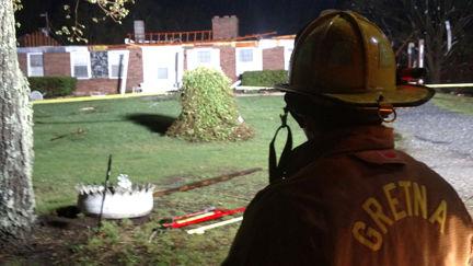 A Gretna firefighter surveys damage of a home on Burke Rd.
