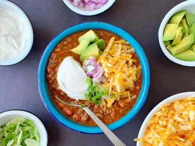 Lots of crunchy, sharp and creamy toppings turn a simple bowl of beef and chili into dinner in an instant.
