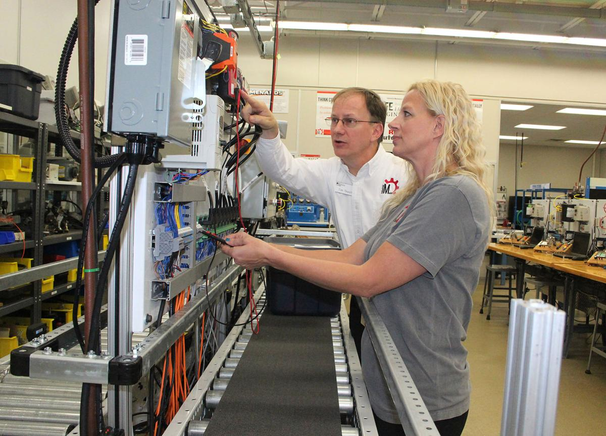 Tim Tewalt, program director for Chippewa Valley Technical College in  industrial mechanics, instructs Marcy Madson of Menomonie in this undated  photo.