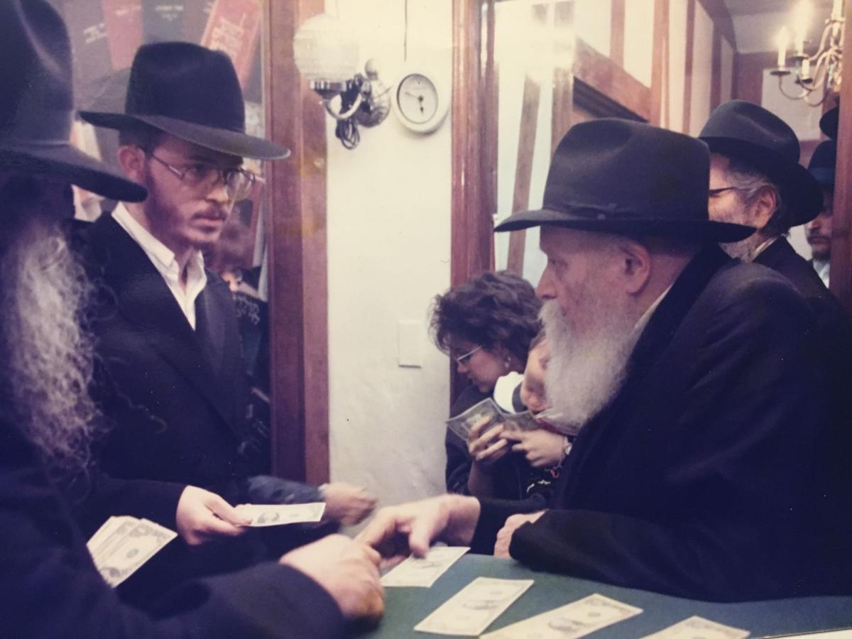 Rabbi Zushe Greenberg receives a dollar and a blessing from Rabbi Menachem M. Schneerson in 1991.