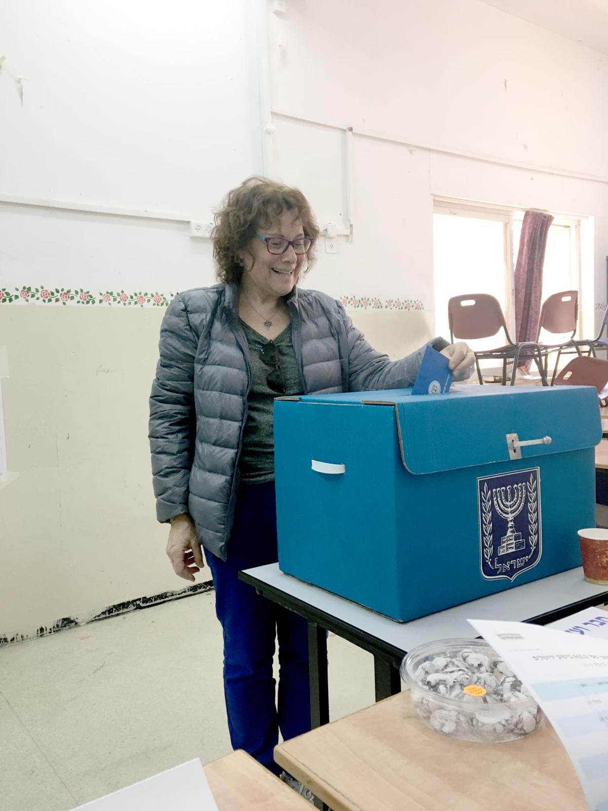 Julie Auerbach places her envelope and ballot in the ballot box.