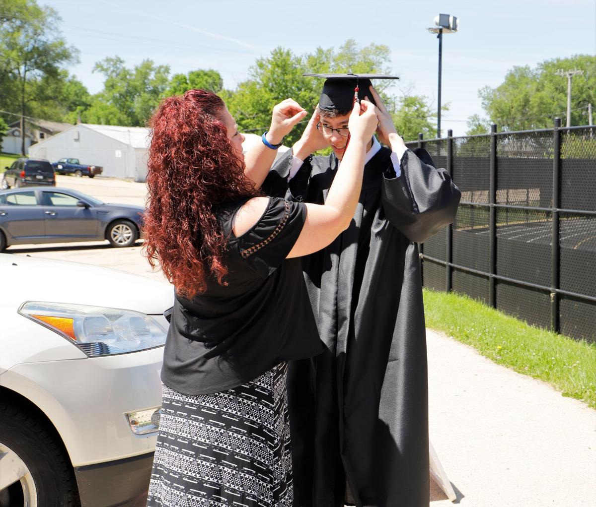 Ethan Nielsen gets help with his cap from his mother, Shannon
