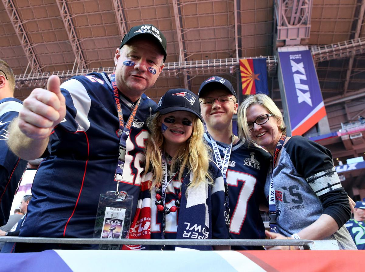 Steve Gorham, of Andover, Massachusetts, gives a thumbs up with his family Brigitte, 12, Oliver, 16, and wife Dodie before the start of Super Bowl XLIX.